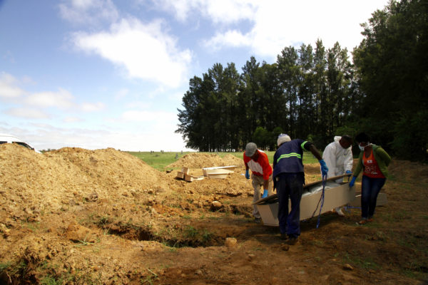 "Undertakers from Today's Hope funeral parlour conduct a pauper's burial at Doornkop Cemetery in Soweto. The cemetery began burying ""paupers"" last year."